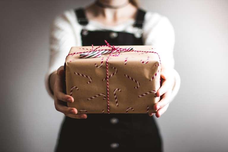 Nainen ojentaa joulupakettia, Lahjoita mielenterveystyöhön, Mielenterveyden keskusliitto